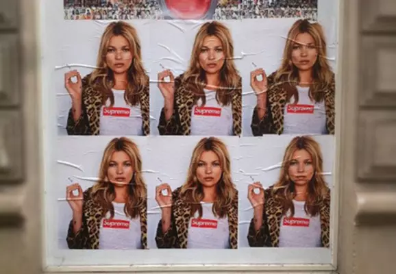 Photo of a street ad showing a woman wearing Supreme branded clothing